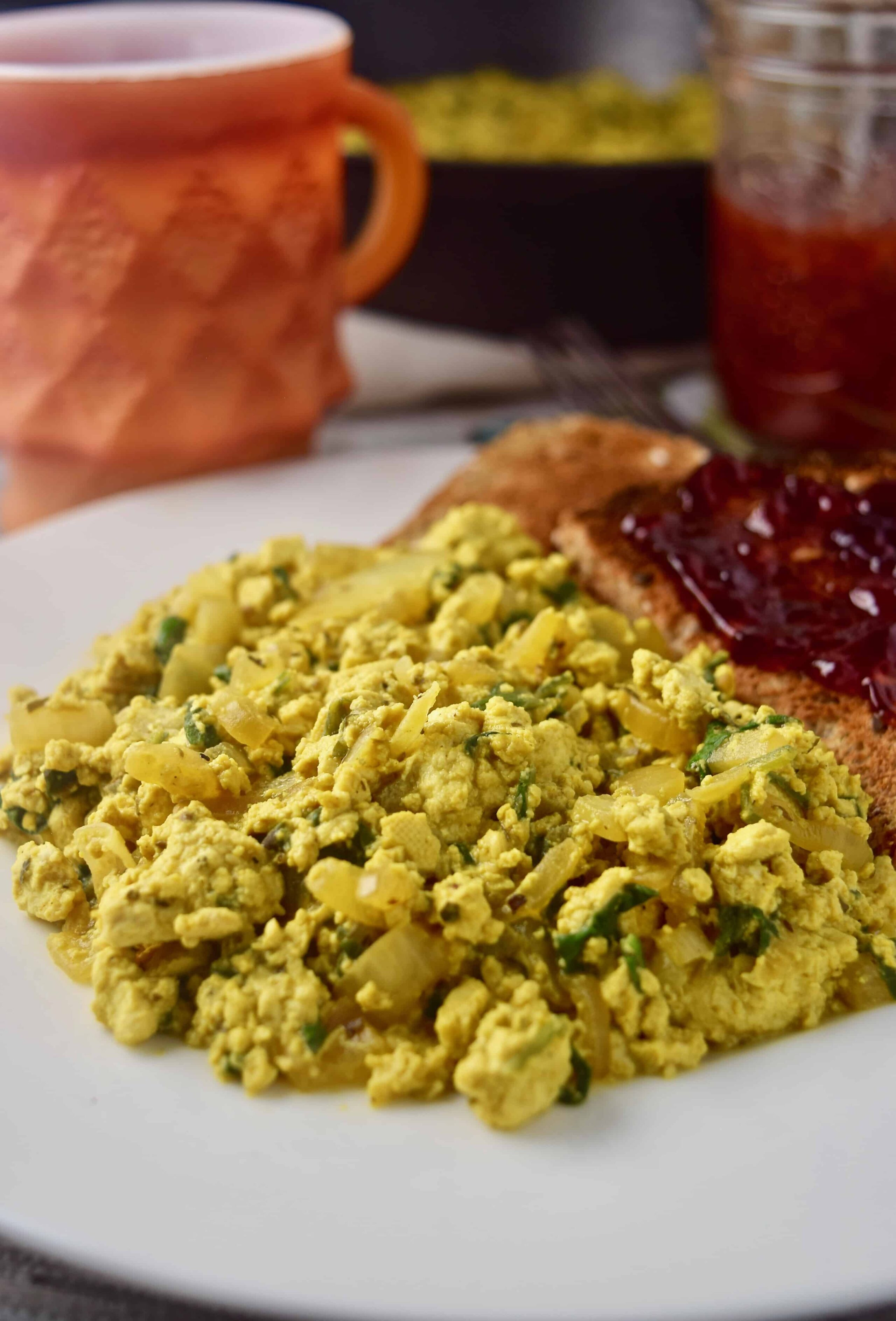 Tofu scramble on plate with toast and cup of coffee.