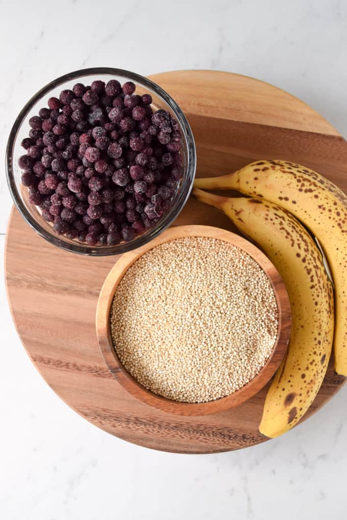 blueberries, bananas, and uncooked quinoa on cutting board.