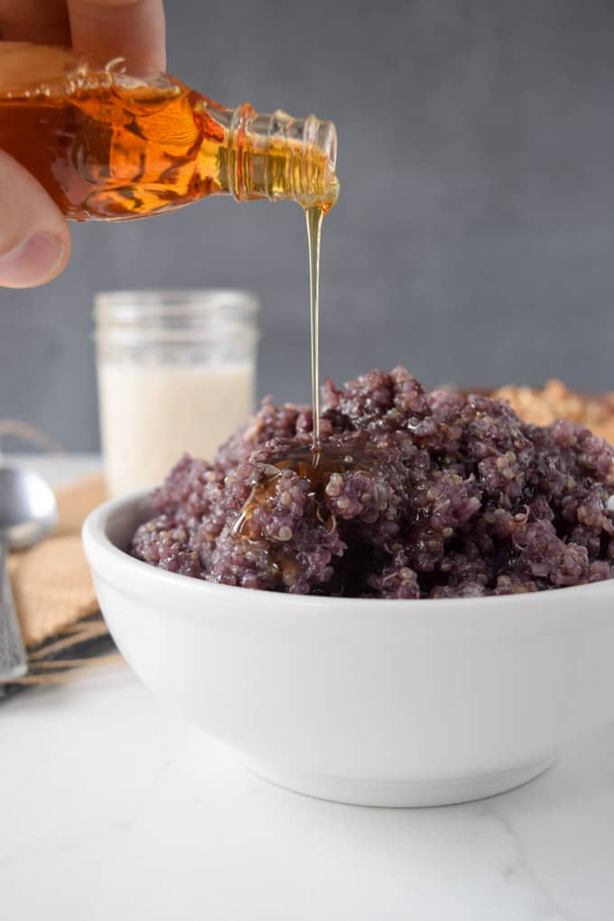 Syrup being poured on top of blueberry quinoa.