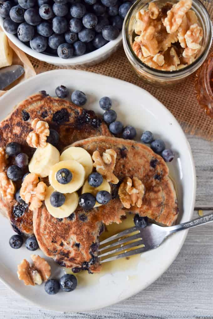 Blueberry and banana pancakes with fork and maple syrup.