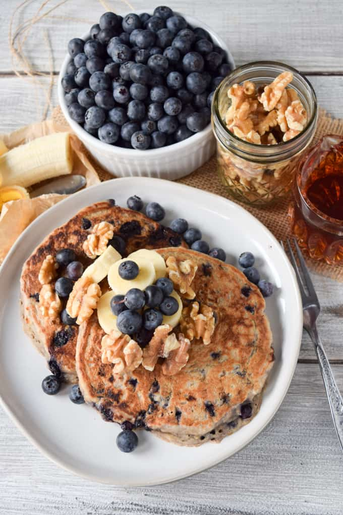 Vegan blueberry banana pancakes on a plate with blueberries and nuts.