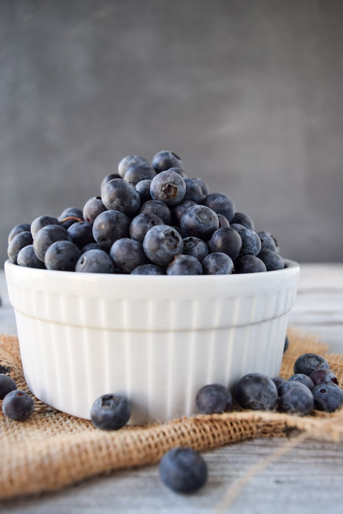 White bowl of blueberries on burlap cloth.