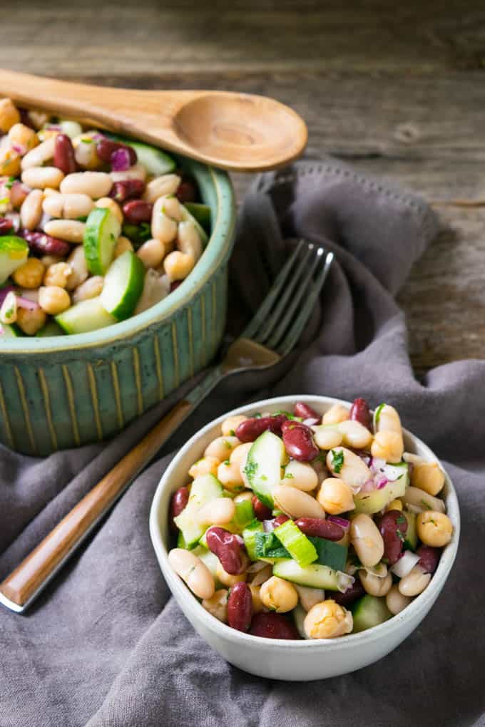 two bowls of three bean salad on napkin with a fork