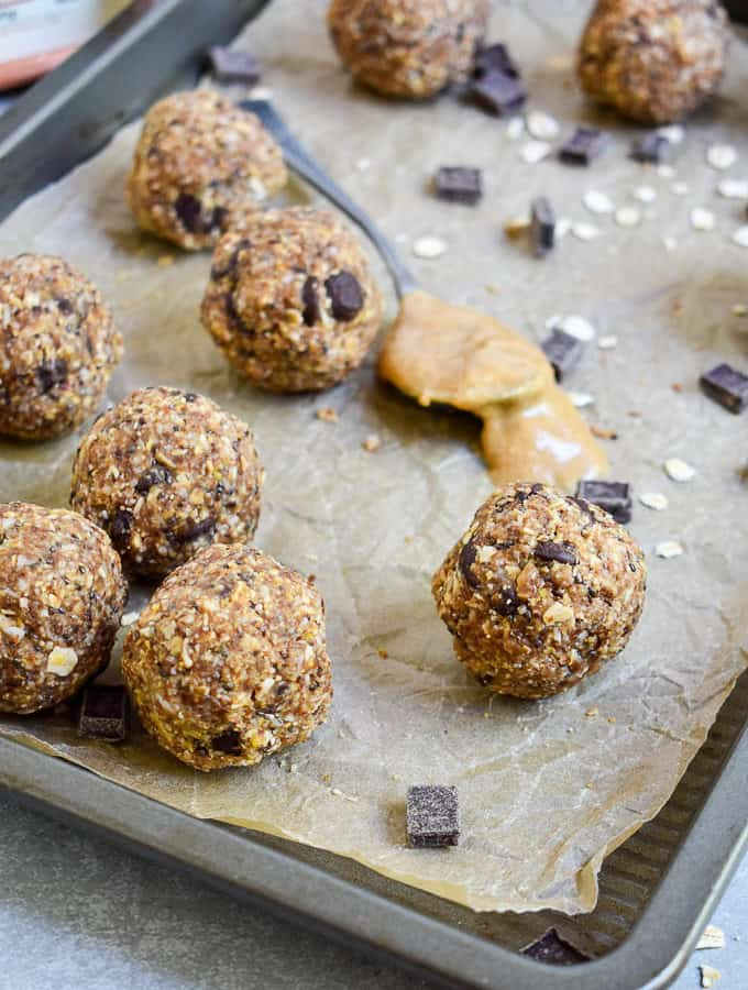 Peanut Butter Protein Energy Bites on cookie sheet with chocolate chips and peanut butter spoon.
