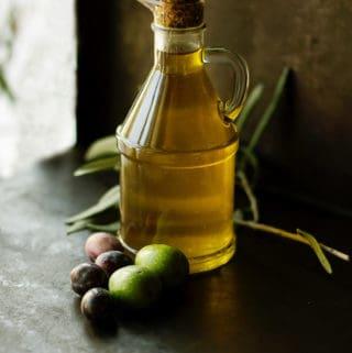 Bottle of olive oil on table.