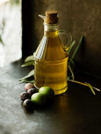 Bottle of olive oil on table.