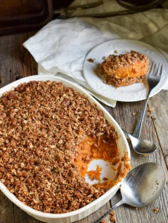 Crunch Pecan Sweet Potato Casserole on table with serving dish and plate