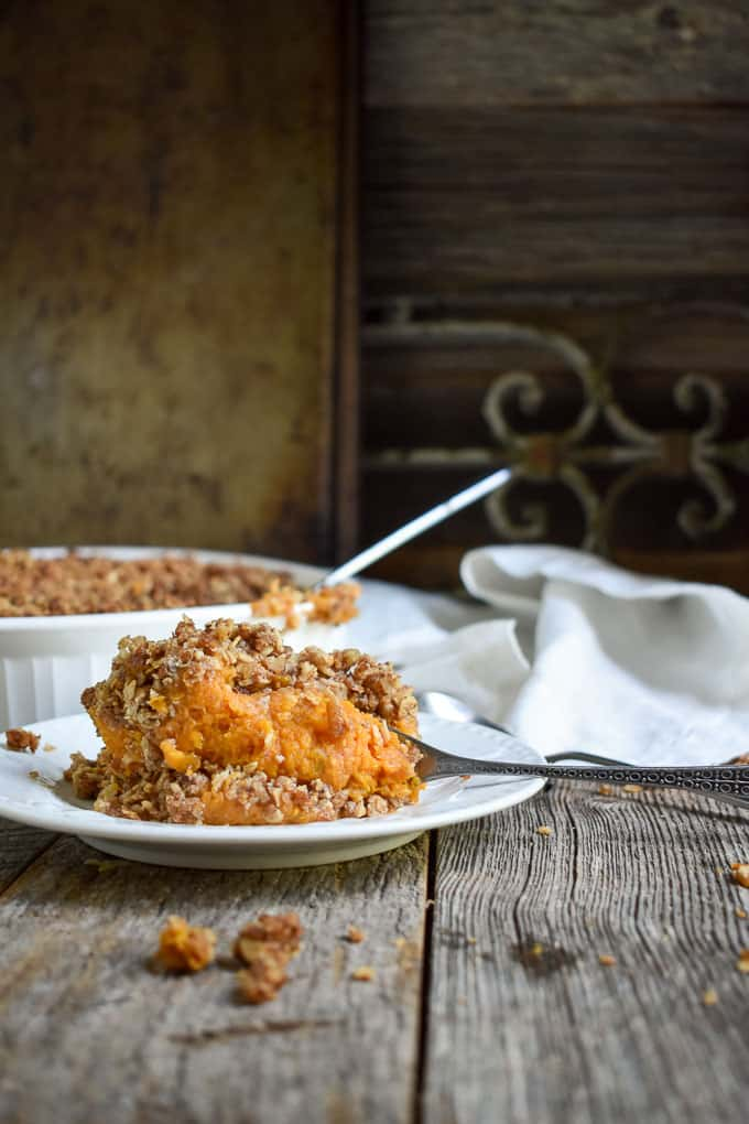 Crunchy Pecan Sweet Potato Casserole on plat with a fork.