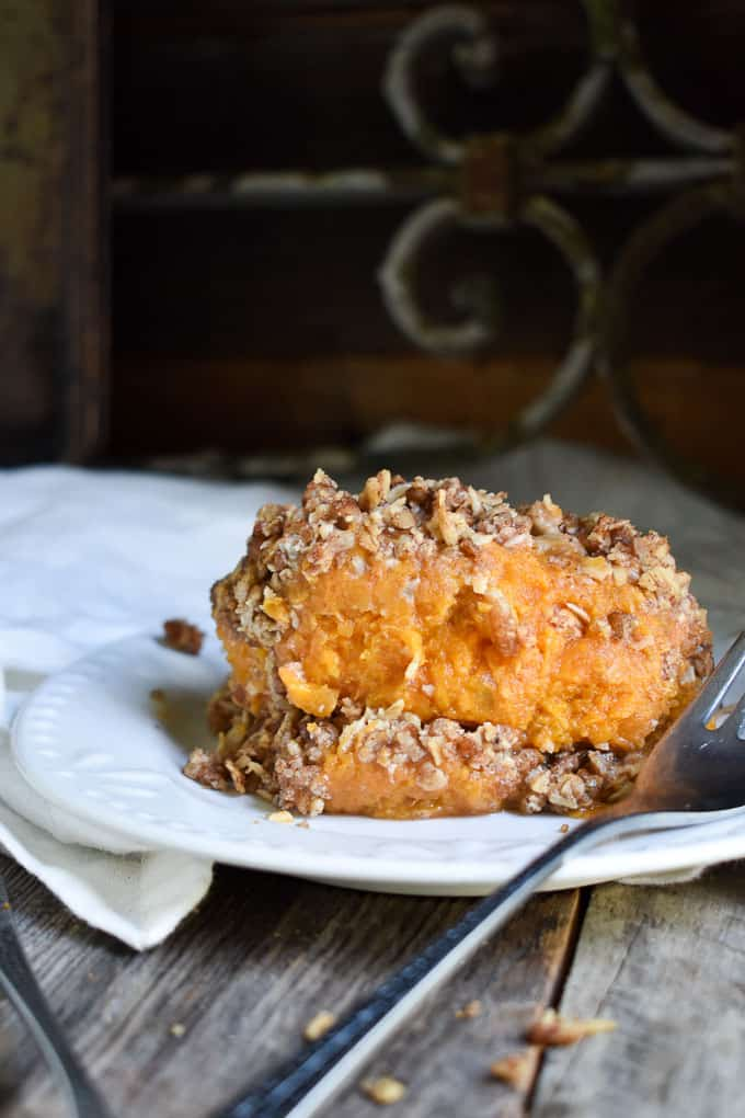 Crunchy Pecan Sweet Potato Casserole on plate with fork and napkin.
