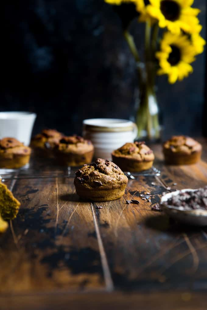 Chocolate chip muffins on table with flowers.