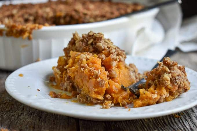 Sweet Potato Casserole on plate with serving dish.