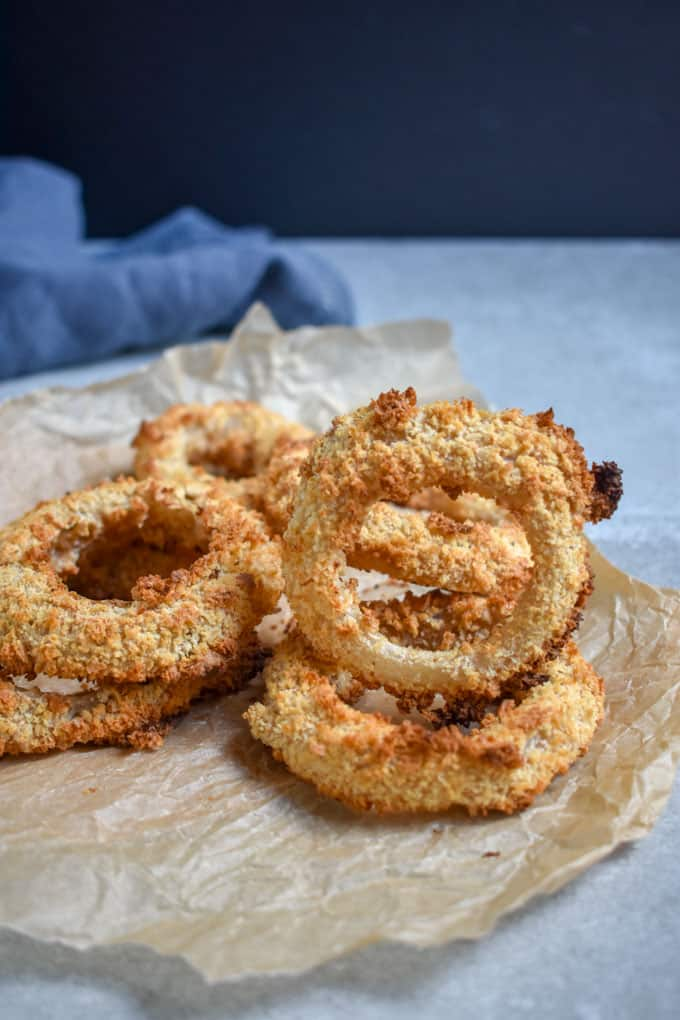 Crunchy baked onion rings balanced on table.