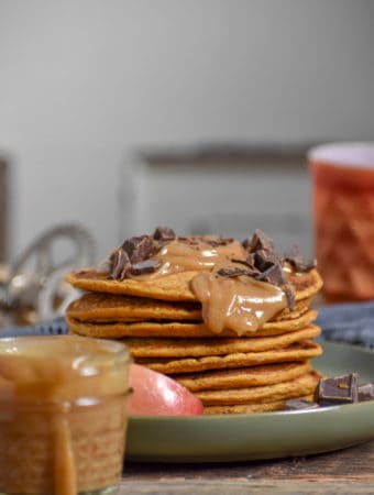 Vegan pumpkin pie pancakes on table with coffee and caramel.