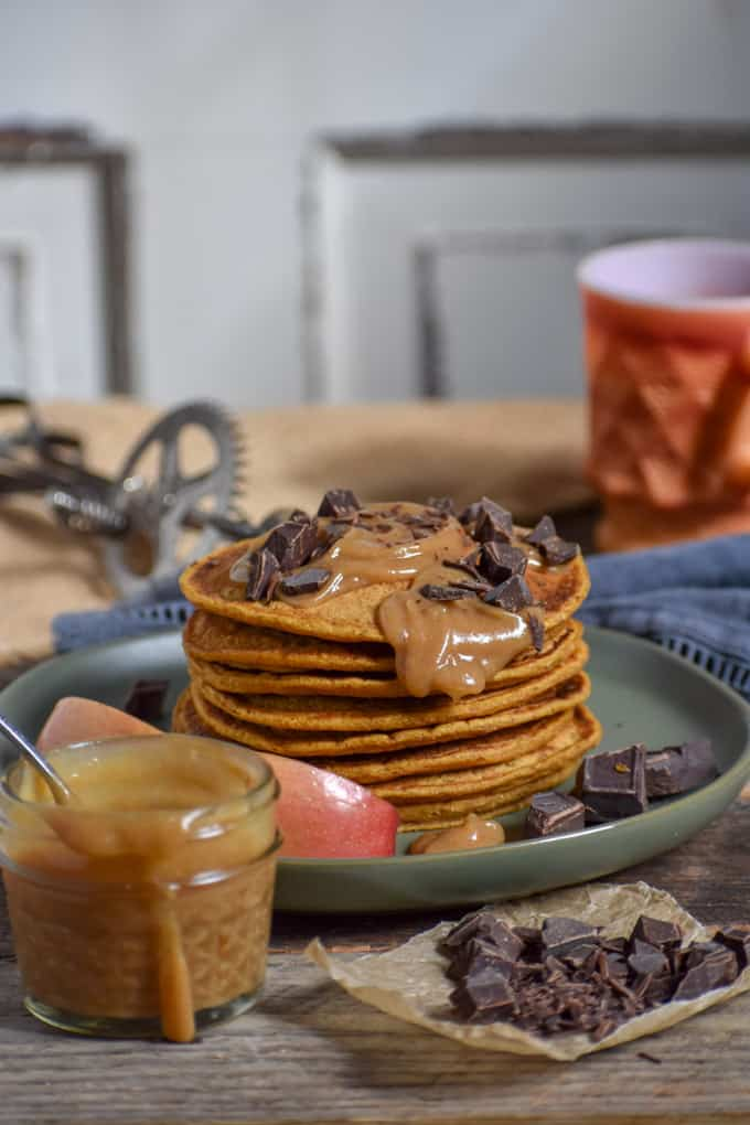 Vegan Pumpkin Pie Pancakes on table with caramel and chocolate chunks.