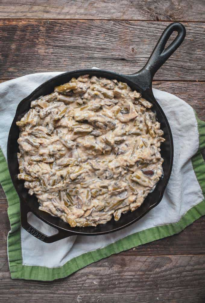 Vegan green bean onion ring casserole in a cast iron skillet.