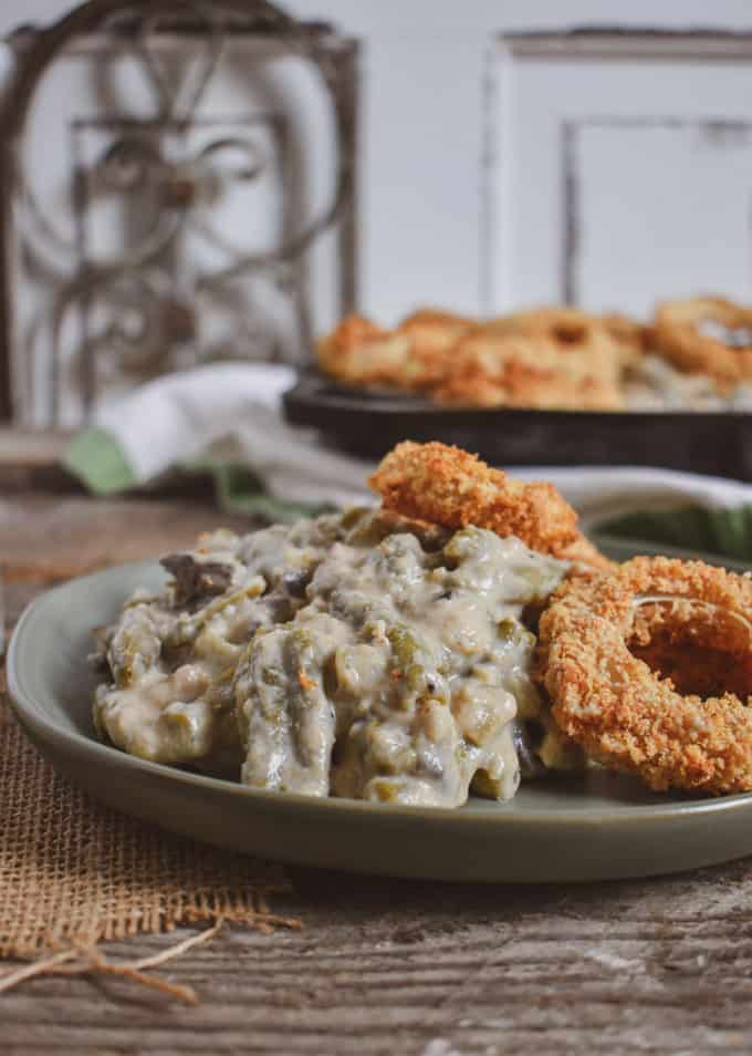 Vegan green bean onion ring casserole on plate and cast iron skillet.