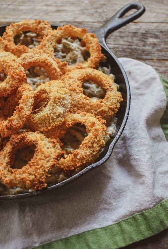 Vegan green bean casserole with onion rings in cast iron skillet in front of window.