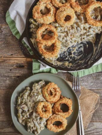 Vegan green bean onion ring casserole on a plate and in cast iron skillet.