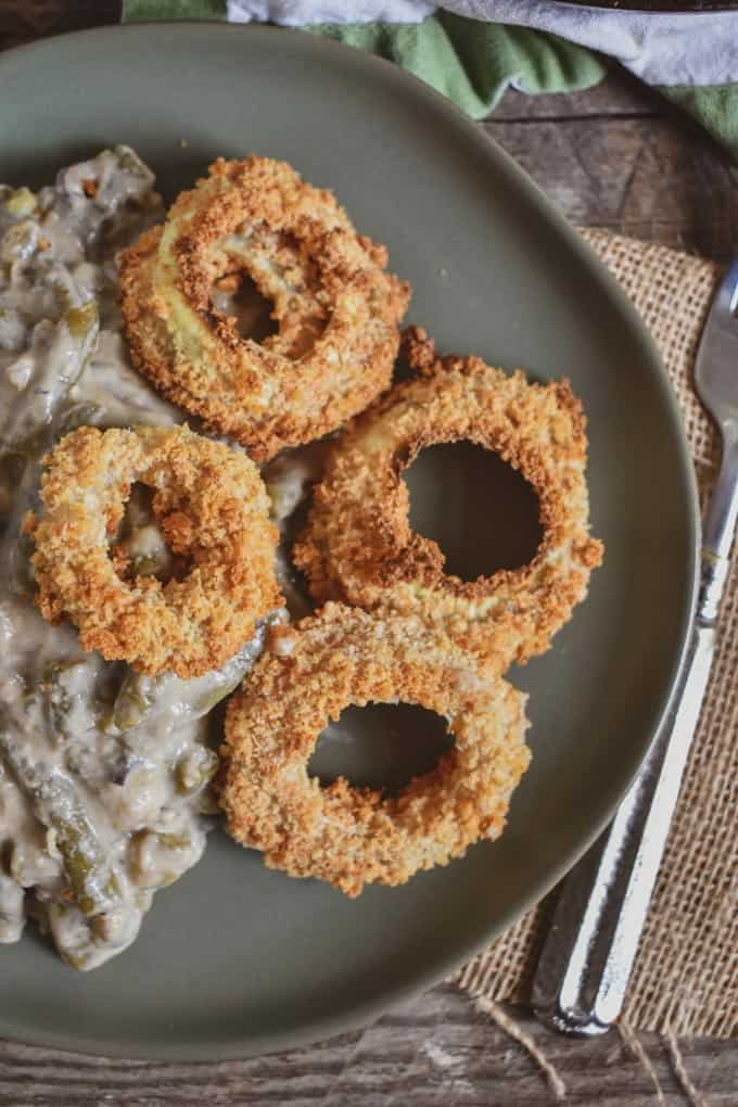 Vegan green bean onion ring casserole on plate with onion rings on side.