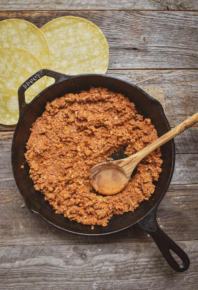 Cauliflower mushroom walnut vegan taco meat in cast iron skillet with a wooden spoon.