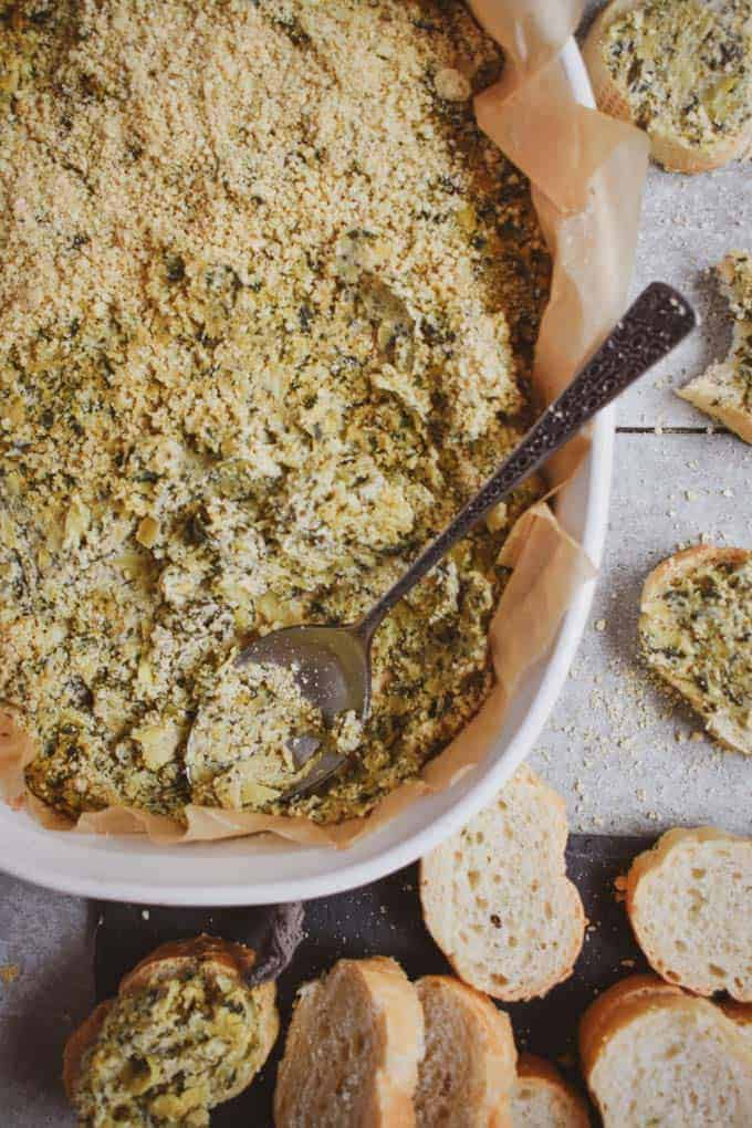 Creamy vegan spinach artichoke dip with spoon and bread.
