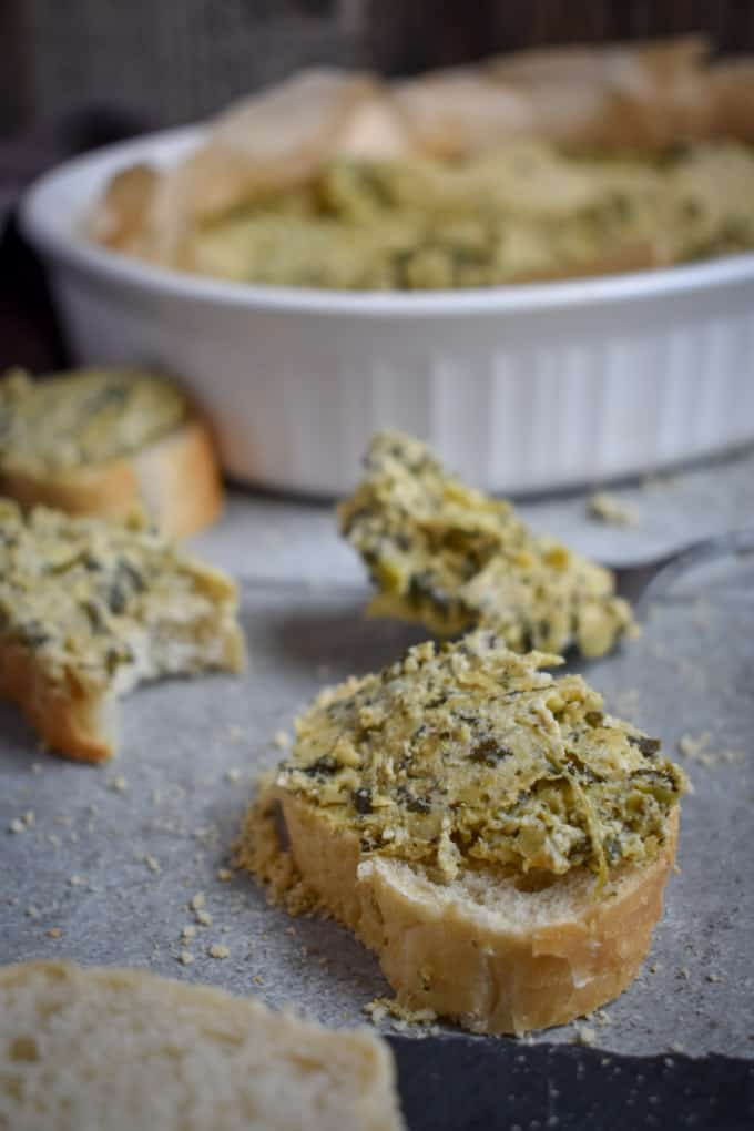 Creamy vegan spinach artichoke dip on bread.