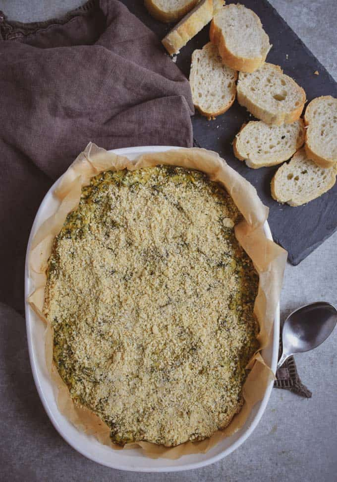 Creamy vegan spinach artichoke dip with vegan parmesan in baking dish.