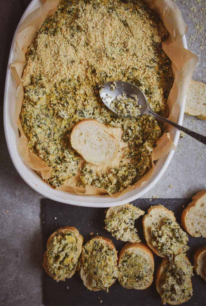 Vegan spinach artichoke dip and bread in bowl.