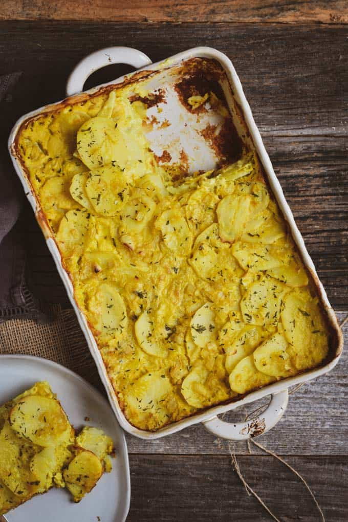 Creamy vegan scalloped potatoes on table with plate.