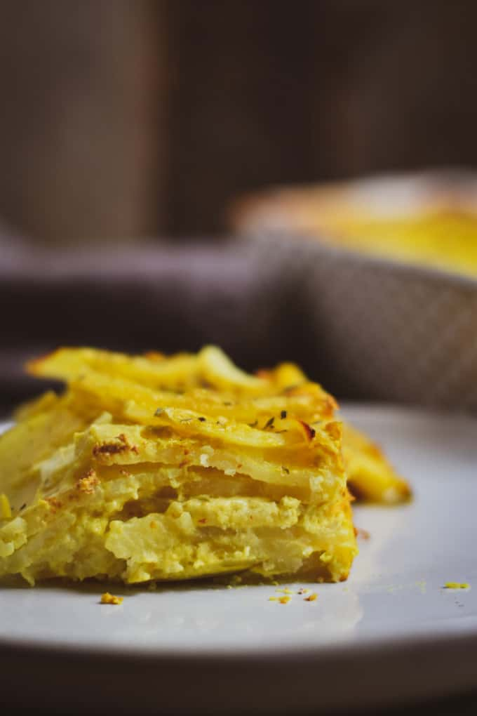 Creamy vegan scalloped potatoes on stacked on plate.