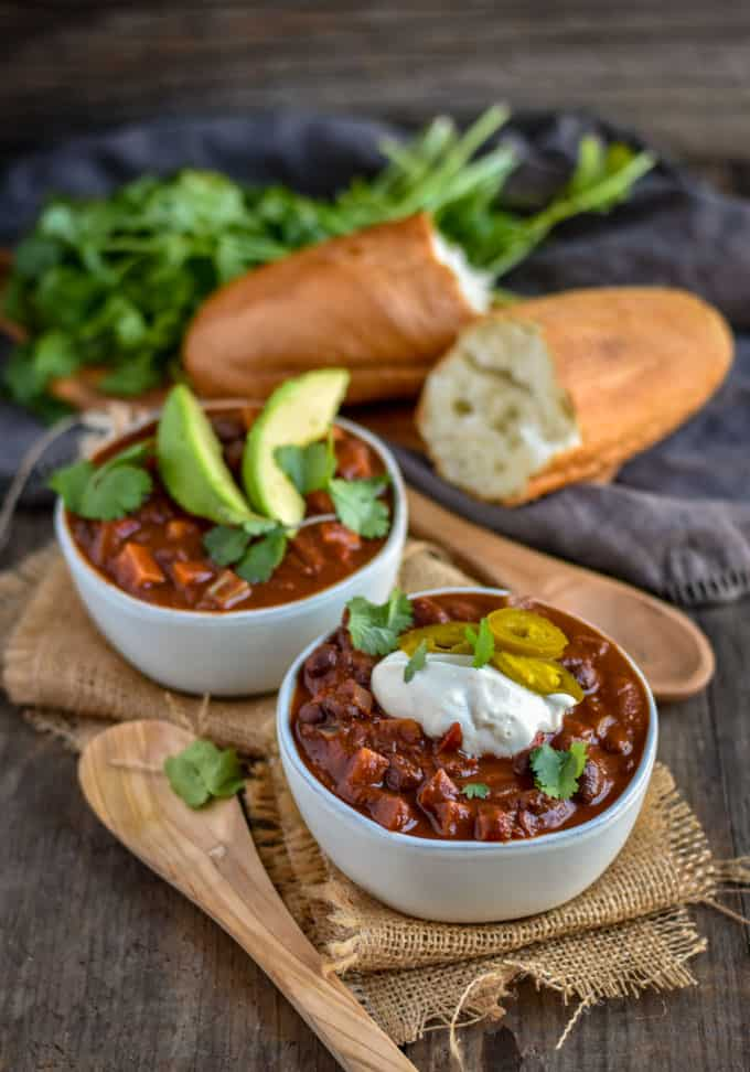 Sweet potato black bean chili on table with spoon and bread.