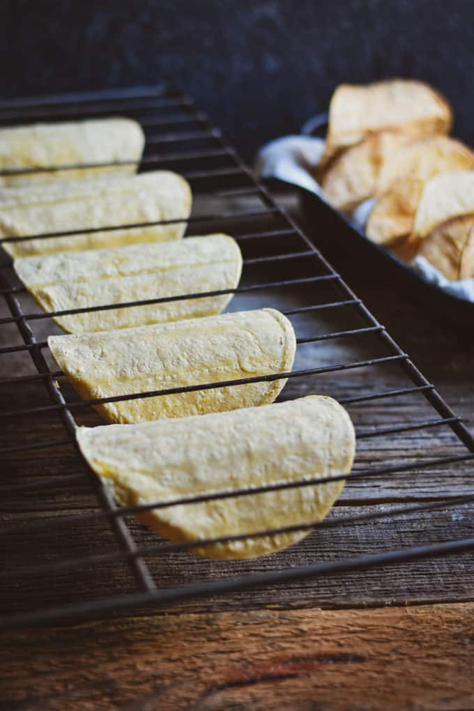 Crunchy baked taco shells tortillas on oven rack.
