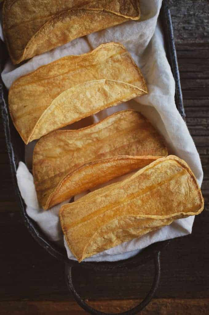 Crunchy baked taco shells in basket with white napkin.