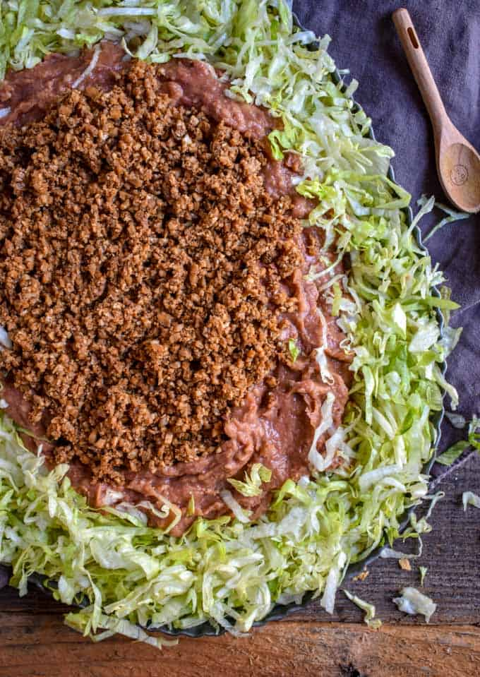 Cauliflower Taco Meat, beans and lettuce on platter for Mexican Seven Layer Dip recipe.