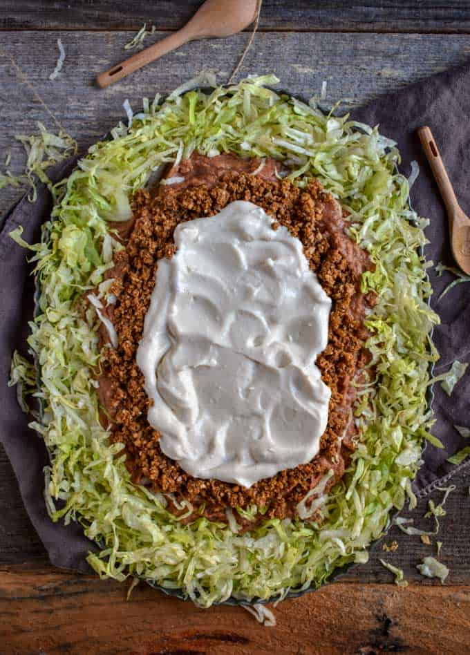 Cauliflower Taco Meat, tofu sour cream, beans and lettuce on platter for Mexican Seven Layer Dip recipe.