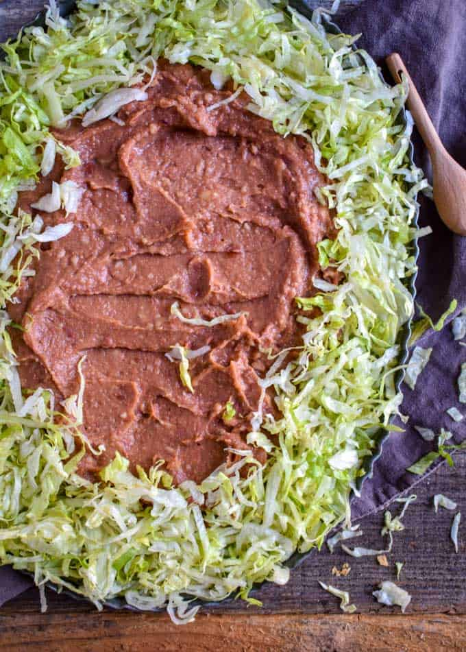Mexican Seven Layer dip refried beans and lettuce on platter.