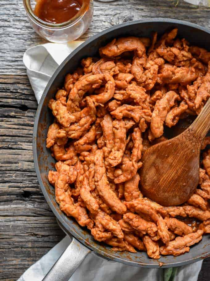 Quick and Easy BBQ Soy Curls in pan with wooden spoon.