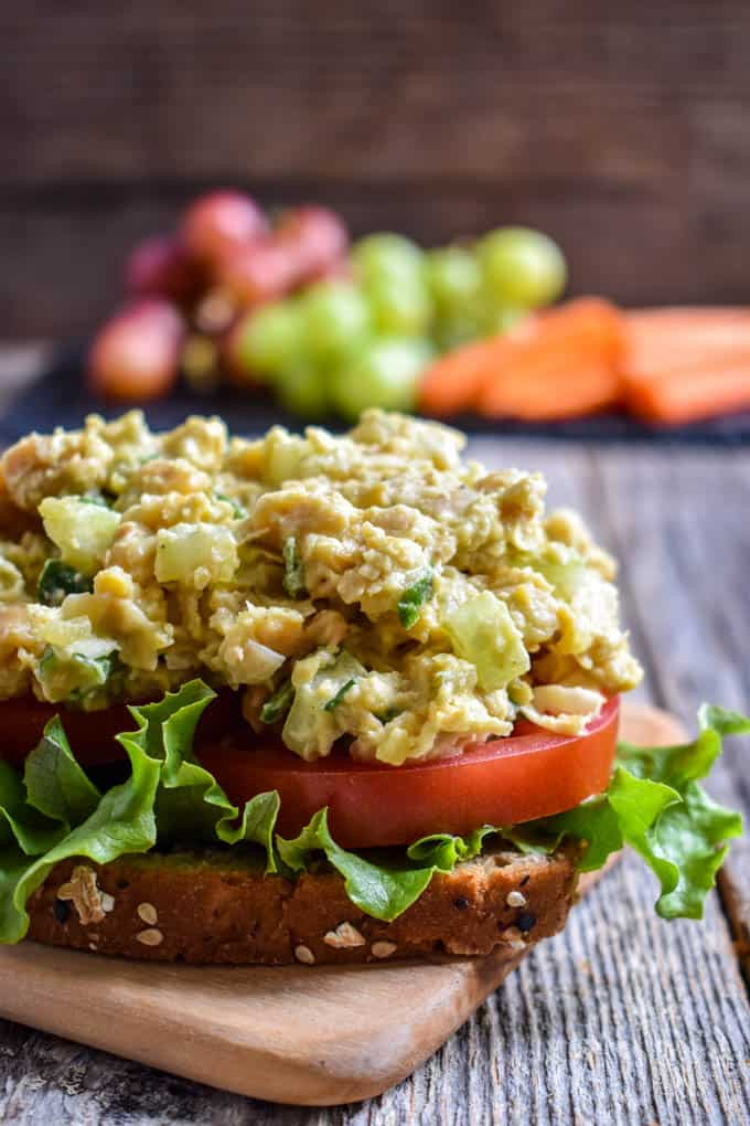 Chickpea Salad Sandwich with lettuce and tomato without top piece of bread.