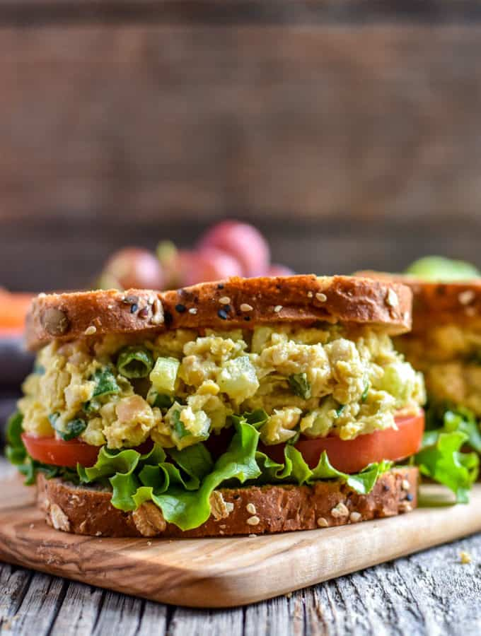 Chickpea Salad Sandwich with lettuce and tomato on cutting board.