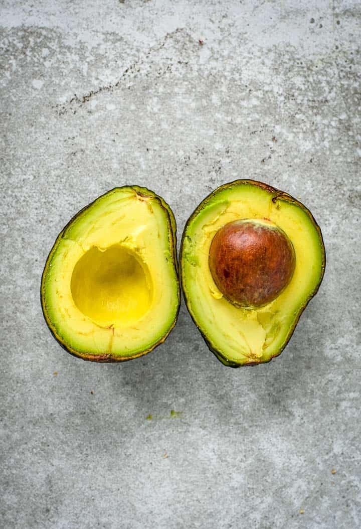 Avocado split in half on table.