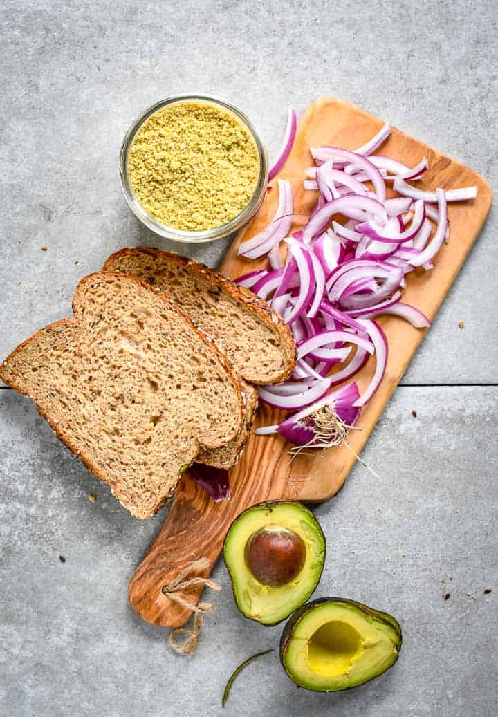two slices of bread, parmesan, red onions, and avocado on cutting board.