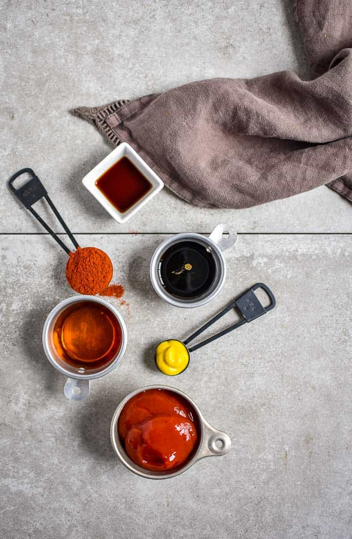 bbq sauce ingredients on counter top with gray dish towel.