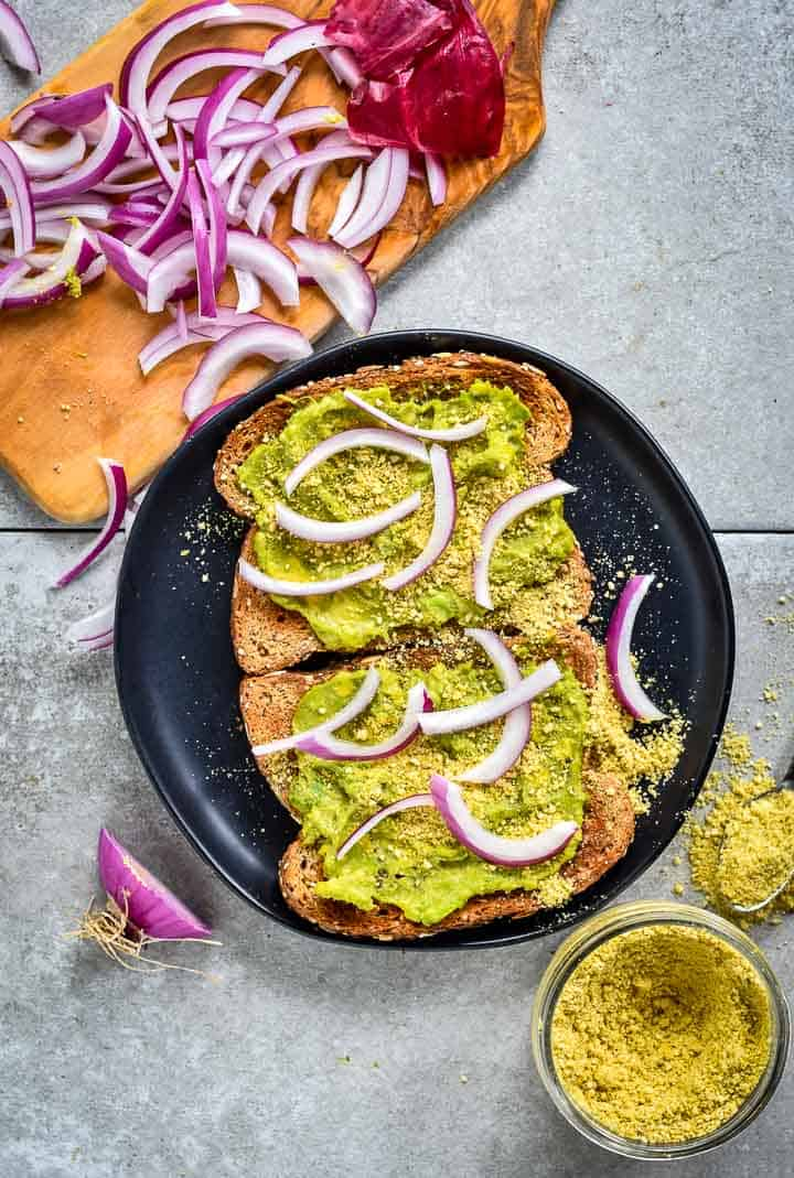 Easy vegan avocado toast on plate with vegan parmesan and red onion slices.