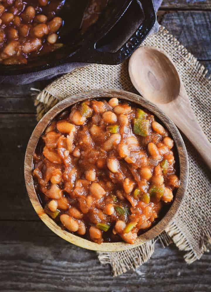 Easy barbecue baked beans in wooden bowl with wooden spoon