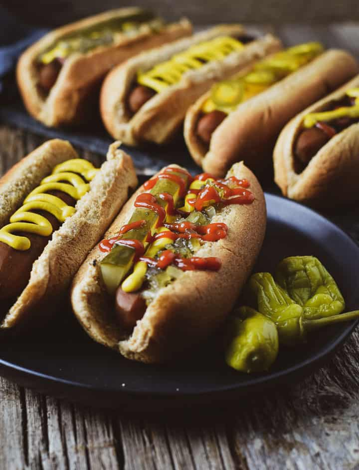 Two carrot dogs on black plate in front of four carrots dogs.