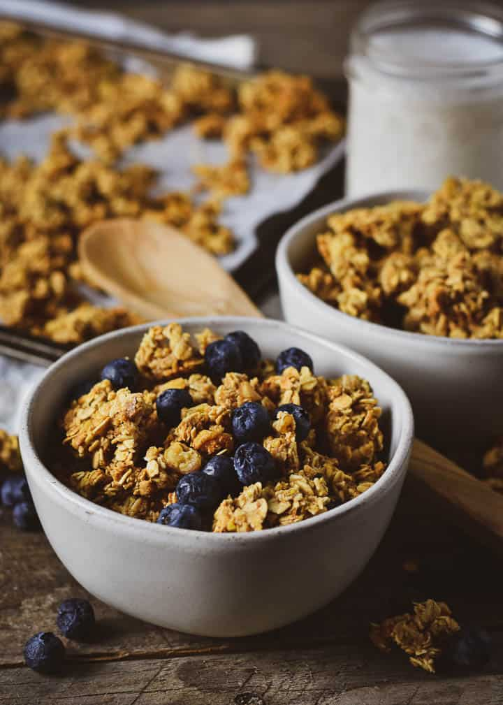 Granola in bowl with blueberries with baking sheet and glass of milk.