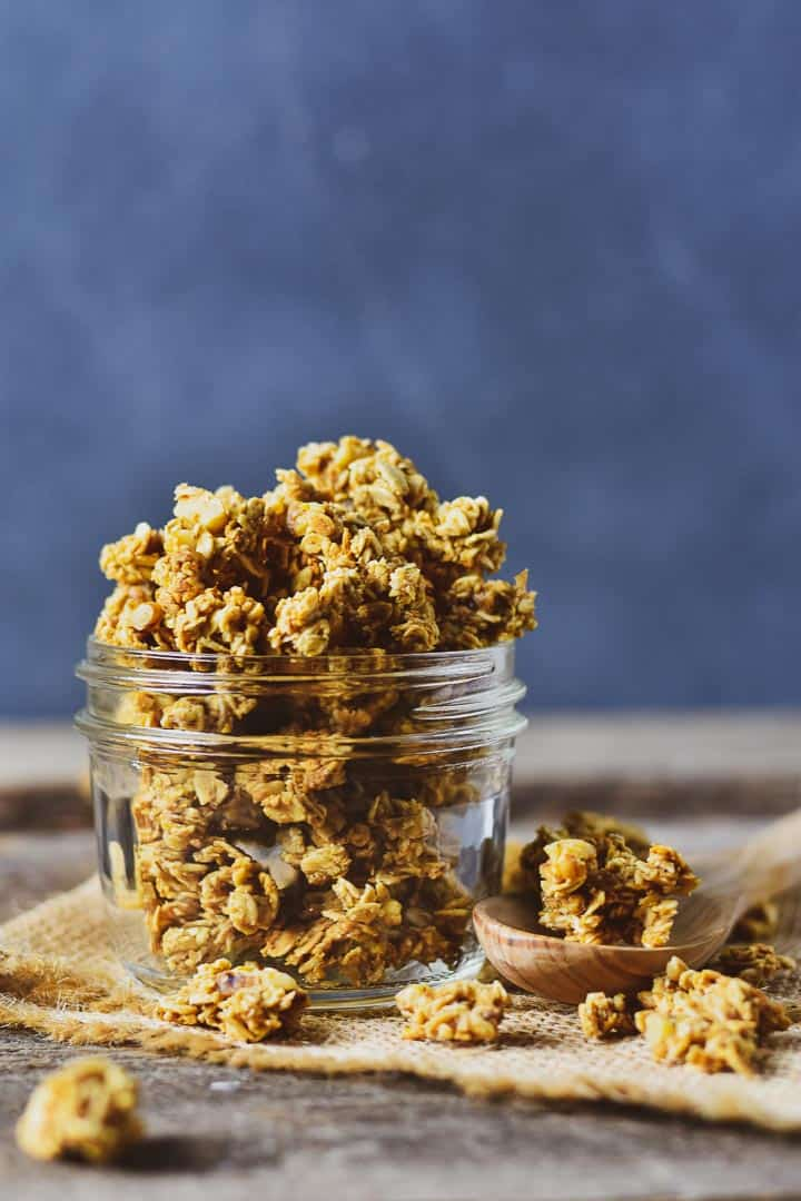 Healthy oil-free granola in a glass jar on burlap with a wooden spoon on the side.
