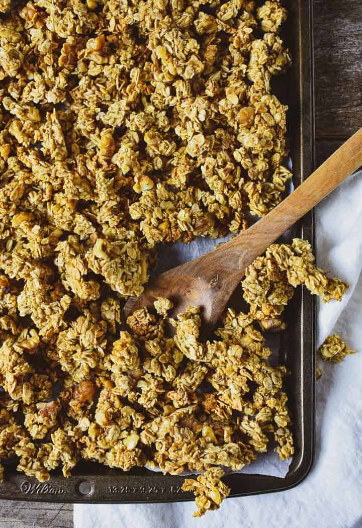 Granola on a baking sheet on top of white napkin with a wooden spoon.