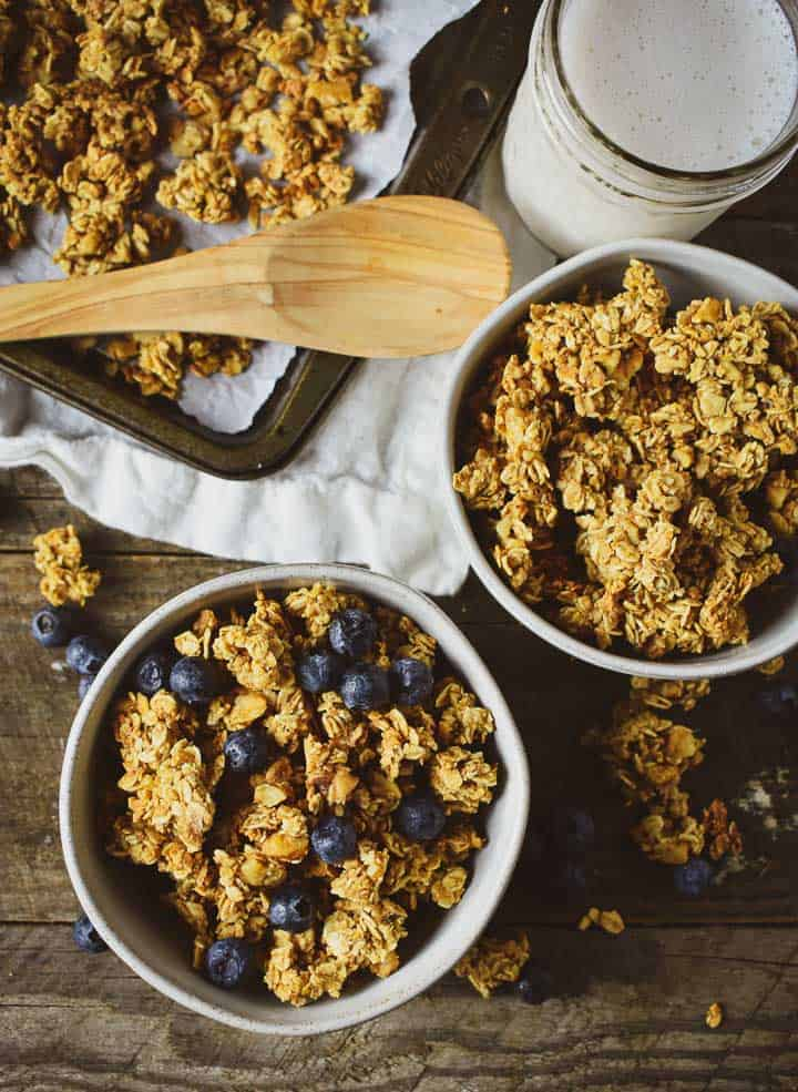 Two bowls of healthy oil-free granola on wooden table with blueberries and milk.