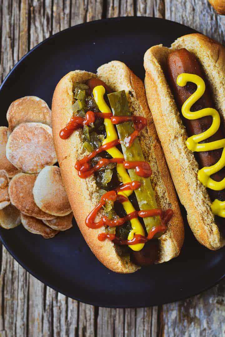 Vegan carrot dog with relish, ketchup, mustard, and pickle and one with mustard only on plate with chips.